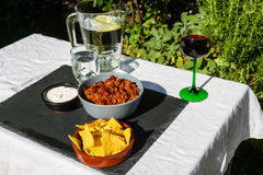 Chilli Con Carne in ceramic bowl with tortilla chips and iced wa Royalty Free Stock Photo