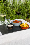 Chilli Con Carne in ceramic bowl with tortilla chips and iced wa Royalty Free Stock Images