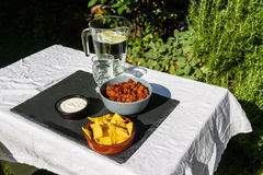 Chilli Con Carne in ceramic bowl with tortilla chips and iced wa Stock Image