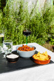 Chilli Con Carne in ceramic bowl with tortilla chips and iced wa Stock Images