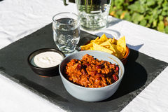 Chilli Con Carne in ceramic bowl with tortilla chips and iced wa Royalty Free Stock Image