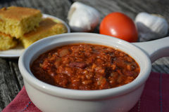Chilli with cornbread. A bowl of chilli in the forground with cornbread in the background Royalty Free Stock Images