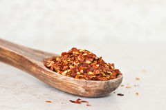 Chilli Flakes. Red hot chilli flakes on a wooden spoon on a light colored counter top Stock Photography