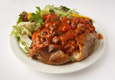 Chilli Jacket Potato with side salad. A beef chilli baked potato on a plate with side salad Royalty Free Stock Image