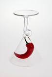 A chilli pepper under wine glass. A red chilli pepper under wine glass Royalty Free Stock Photo