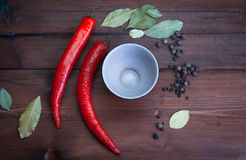 Chilli peppers and spices on dark wood with empty cup. Chilli peppers and spices on dark wood with empty phial cup Royalty Free Stock Photo