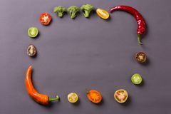 Chilli peppers with tomatoes and broccoli on grey background compose frame Royalty Free Stock Photo