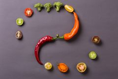 Chilli peppers with tomatoes and broccoli on grey background Stock Photo