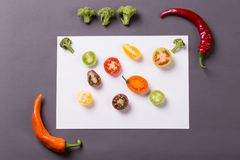 Chilli peppers with tomatoes and broccoli on grey and white background stock photos