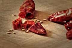 Chilli seeds and sliced chilli pods on a chopping. Sliced, dried, red serrano (Sport) chilli peppers on a chopping board with scattered chilli seeds. Knife Royalty Free Stock Photos