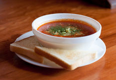 Chilli soup. Red chilli soup served in a white bowl with toast bread royalty free stock photo