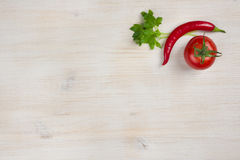 Chilli and tomato with greens on bleached wooden board Stock Photography