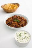Chilli, tortillas, and sour cream on white. A bowl of chilli-con-carne on a white tablecloth with side dishes of tortilla chips and sour cream with chives Royalty Free Stock Photos