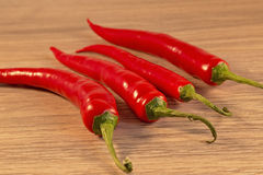 Chillie. Red Chillies shown lying on a wooden background Stock Photos