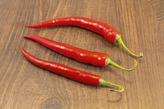 Chillie. Red Chillies shown lying on a wooden background Royalty Free Stock Photo