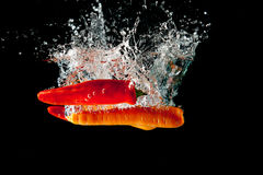 Chillies and Carrots Water Splash. Chillies and carrots drop in a water tank creating a splash Royalty Free Stock Images
