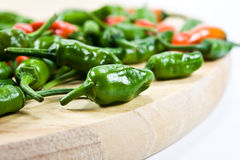 Chillies on chopping board. Apache chillies on round chopping board Stock Image