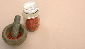 Chillies. This photo shows sun dried Birds Eye chilies in a  preserve bottle and in a stone pestle ready for use in the kitchen Stock Photos