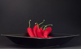 Chillies on a plate. Bunch of chillies on a black plate Royalty Free Stock Photos