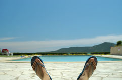 Chillin by the pool. Feet with the blue sky in the background Royalty Free Stock Photos