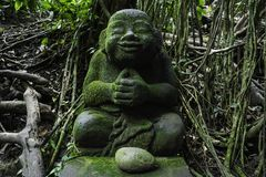 Chilling buddha statue in green, Bali monkey forest stock photo
