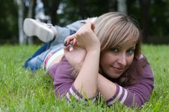 Chilling on a grass. Young beautiful girl is laying on a grass royalty free stock images