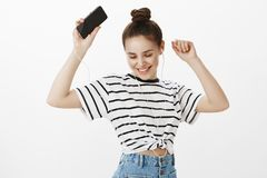 Chilling with great music, making party for her own. Bright good-looking european female student with bun hairstyle. Dancing with raised hands, listening songs Royalty Free Stock Images