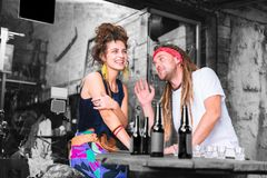 Couple of hippies having rest while chilling and laughing in their favorite bar
