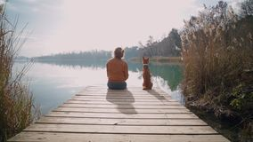 Chilling next to lake with crystal water. Young hipster woman or teenager in brown leather jacket sits on edge of pier or boardwalk with best friend puppy dog stock footage