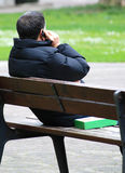 Chilling and phoning. A young man is making call in park, sitting on a bench Stock Images