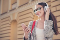 Chilling on the sun. Young attractive girl is listening to the m stock image