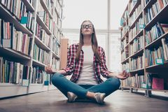 Chilling, wellbeing, vitality, peace, wisdom, education, campus. Lifestyle. Low angle shot of young calm nerdy girl, practicing yoga in the lotus position on Stock Images