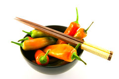 Chillis in a Black Bowl with Chopsticks. Mixed red and green chillis in a black bowl and chopsticks with clipping path on a white background Stock Images