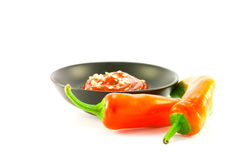 Chillis with Bowl of Chili Sauce. Two red chillis with small black bowl of chili dipping sauce with clipping path on a white background Royalty Free Stock Photos
