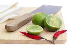 Chillis and lime on chopping board Stock Photos