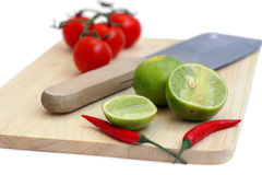 Chillis, lime and tomato on a chopping board and the knife isola Royalty Free Stock Photography