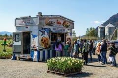 CHILLIWACK, КАНАДА - 20-ОЕ АПРЕЛЯ 2019: люди около тележек еды на фестивале тюльпана на солнечный день стоковые фото