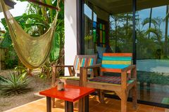 Chillout terrace zone near tropical hotel room with hammock. And wooden chairs Royalty Free Stock Photo