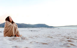 Chilly beach blanket. Cold woman wraps blanket over herself while sitting on the beach after sunset. copyspace provided by panoramic image Royalty Free Stock Image