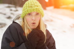 Chilly Blonde Woman in the Snowy Outdoors Wearing Coat and Mittens Stock Photography