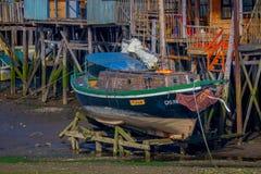 CHILOE, ΧΙΛΉΣ - 27 ΣΕΠΤΕΜΒΡΊΟΥ, 2018: Βάρκα στη χαμηλή παλίρροια μπροστά από τα ζωηρόχρωμα ξύλινα palafitos οικοδόμησης στην ηλιό στοκ φωτογραφία με δικαίωμα ελεύθερης χρήσης