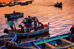 Men in small boats preparing to transfer to trawlers for night fishing on trawlers. Chimbote, Peru - April 17, 2018: Men in small boats preparing to transfer to Royalty Free Stock Photo