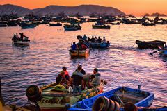 Men in small boats preparing to transfer to trawlers for night fishing on trawlers. Chimbote, Peru - April 17, 2018: Men in small boats preparing to transfer to Stock Photography