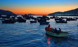 Men in small boats preparing to transfer to trawlers for night fishing on trawlers. Chimbote, Peru - April 17, 2018: Men in small boats preparing to transfer to Royalty Free Stock Image
