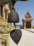 Chime at Buddhist temple. Wind chime at Buddhist temple in Thailand. Background with temple buildings out of focus Stock Photo