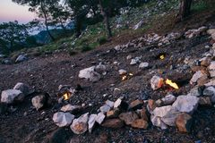 Chimeara`s flames among the rocks next to green grass and trees. Stones on fire made by nature Royalty Free Stock Photography