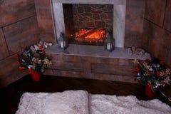 Chimenea adornada con las velas, abeto-conos en la sala de estar w Foto de archivo