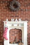 Chimenea adornada de la Navidad en una pared de ladrillo Imagenes de archivo