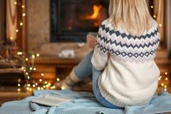 Chimenea cercana relajante de la mujer en la sala de estar adornada Fotografía de archivo libre de regalías