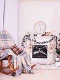 Chimenea de Navidad con la butaca, los relojes y las almohadas Media de la Navidad sobre la chimenea, paisaje de la tarjeta del A imagen de archivo libre de regalías